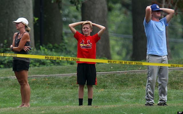 Emotional friends and neighbors stand outside the yellow tape as police detectives work the scene of a murder-suicide in a home in Glendale, Mo., on July 30, 2012.
