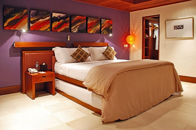 Bedroom with the bed and paintings on the wall at the Villa Asta, Rental Vacation Villa, Bali
