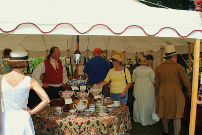 a booth with a white awning and a man selling wares to customers dressed like people from the time of jane austen - early 1800s many tea pots of different colors on display with silverware