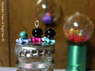 DIY octopus beads; cute little craft using beads and glue. Bottle cap shown for size.