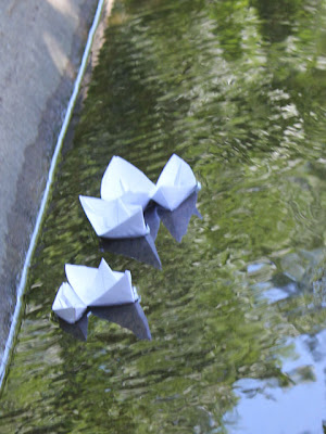 folded paper boats floating in water