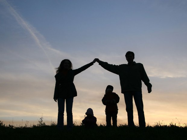 family silhouettes at a sunset