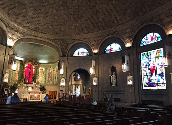 Atmospheric interior of St. Lawrence Basilica with parishioners admiring the splendor