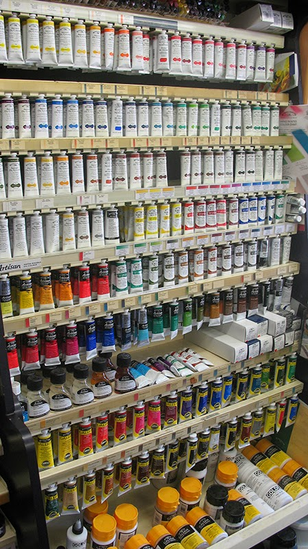 Shelves full of acrylic, watercolour and oil paints