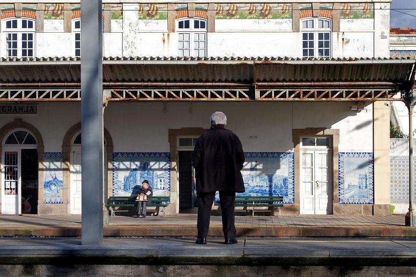 Foto da plataforma de embarque com um homem a meio da imagem, de costas, perto dum pilar em ferro. Ao fundo uma senhora à espera sentada num banco ladeada por painéis cerâmicos de azulejos pintados em tons de azul