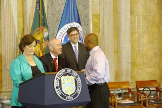 Herbert (right) is congratulated by USCIS Washington, DC District Director Sarah Taylor (left), USCIS Director Alejandro Mayorkas (middle-left), Treasury Secretary Jack Lew (middle-right)