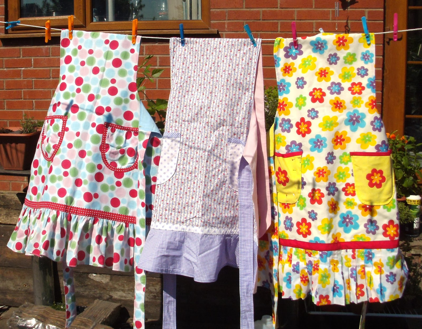 Three colourful aprons on the washing line