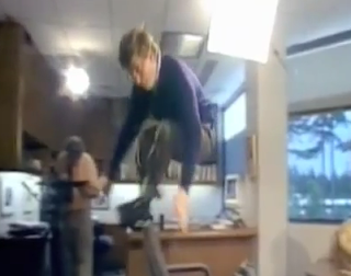 Bill Gates demonstrates his chair jumping skills in front of Connie Chung.