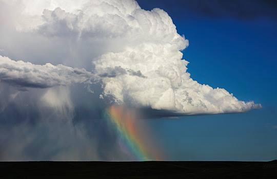 Cumulonimbus cloud over sheets of rain & rainbow