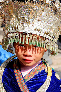 photo of a miao child in traditional costume with silver headdress