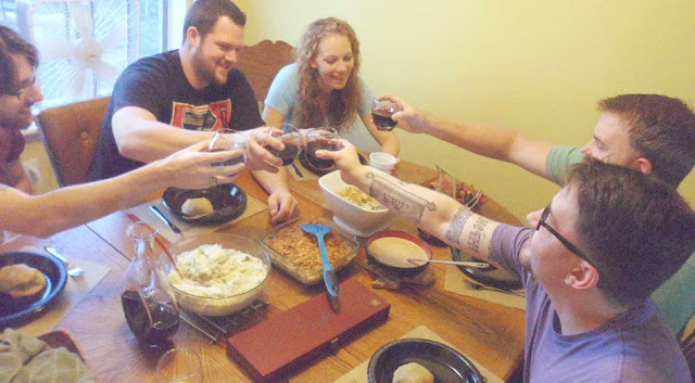 A group of friends toasting with wine over a Thanksgiving feast