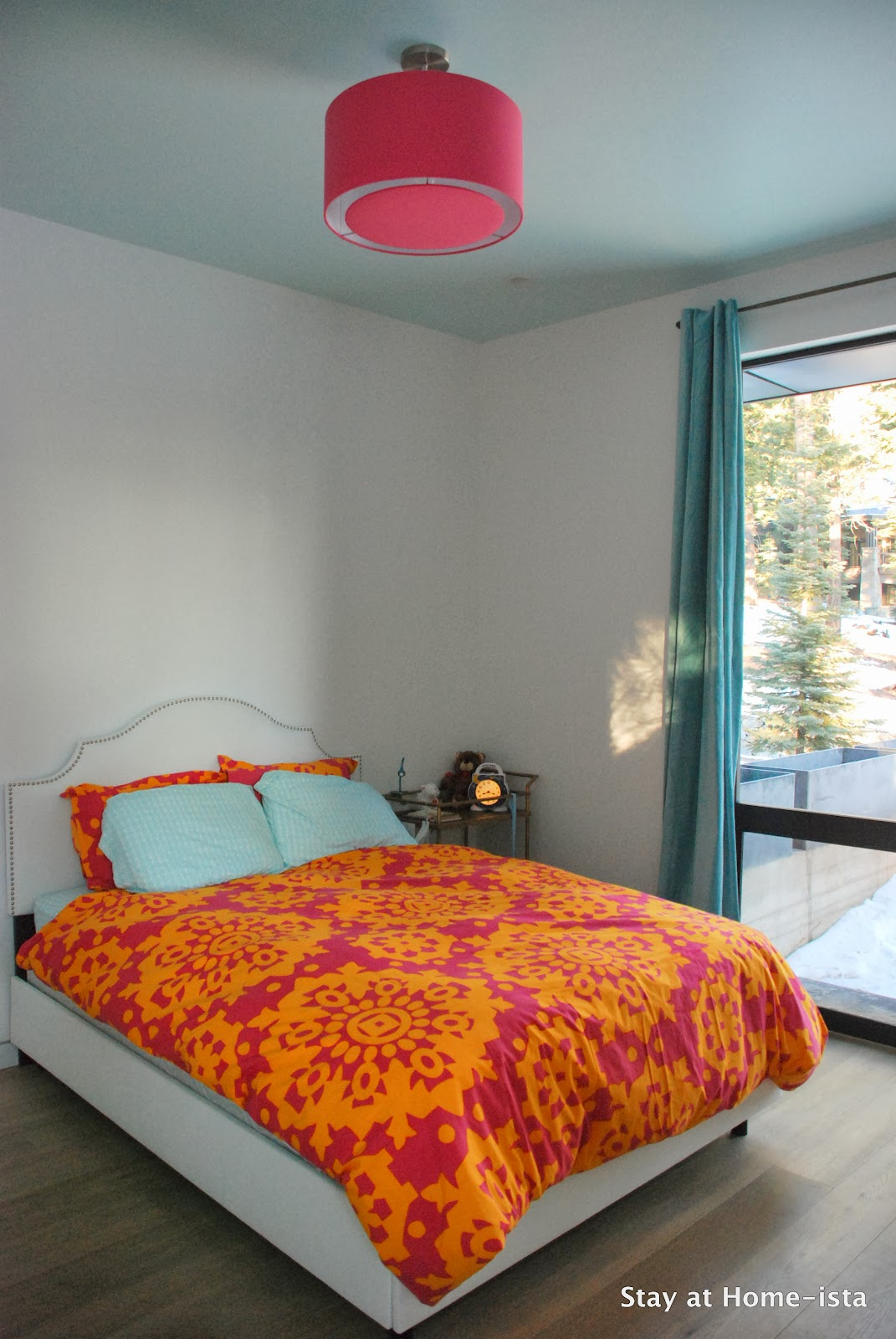 Aqua ceiling, pink drum shade, and pink and orange bedding- such a cute little girl's room.