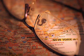 Picture of eyeglasses on a New York map, which magnifies a section of the map.