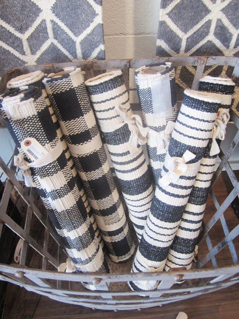 flat weave cotton rugs in navy and white plaids and stripes rolled up in a metal hamper