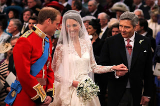 Prince William speaks to his bride, Catherine Middleton as she holds the hand of her father Michael Middleton at the alter of Westminster Abbey.