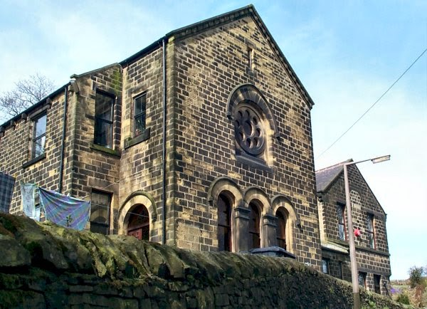 A stone built chapel style building, with a large rose window in the gable end facing the road.  It's current status as a house is betrayed by the line of washing drying to the left and the modern window frames.