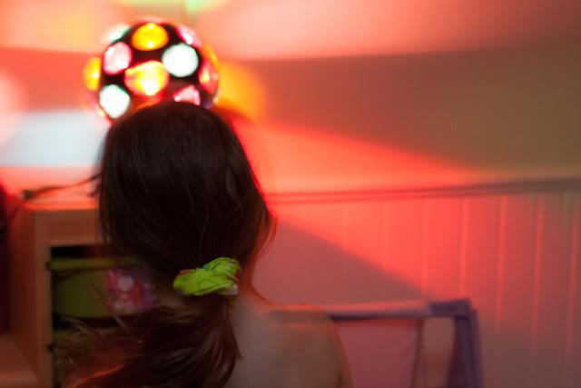 girl dancing in front of disco ball