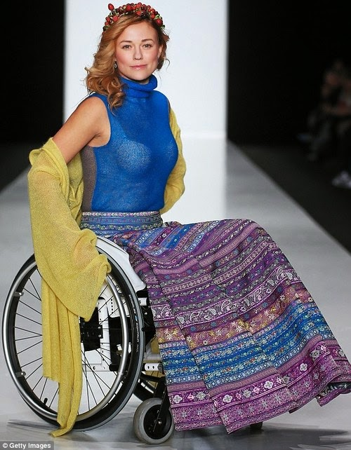 Woman with long blonde hair, in a manual wheelchair, wearing an ornately patterned dress with purples and blues, and a blue top with a light yellow shawl