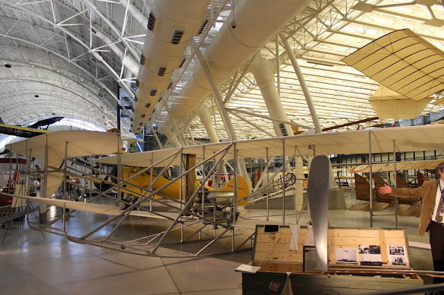 In a very large and well lit airplane hanger (the Smithsonian Institute's National Air and Space Museum Udvar-Hazy Center) sits a replica of the Wright Brothers' Flyer.  The plane is made of wood and features what looks like scaffolding, propellers and a small engine.  Little Star is sitting in the pilot's seat, difficult to see.