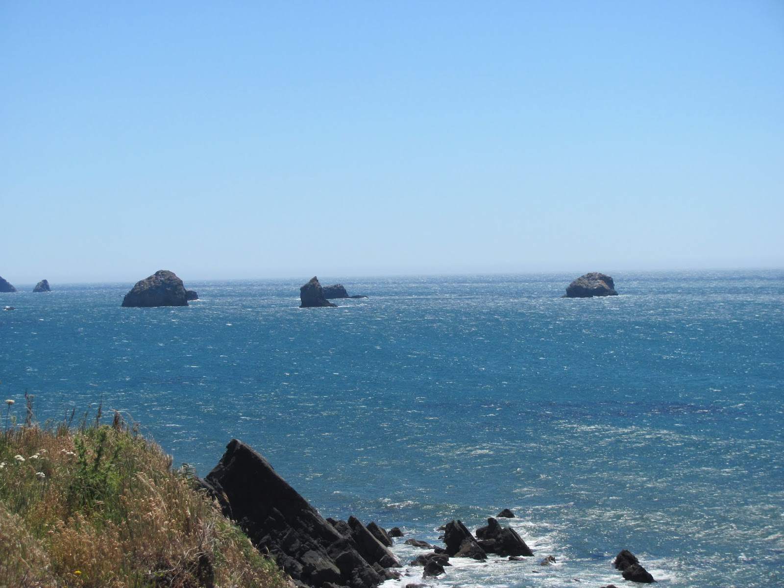 Rocks protrude from the blue water off the beach at Bullards Beach State Park, Oregon