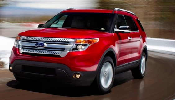 Front 3/4 view of a red 2011 Ford Explorer driving on a wet winding road