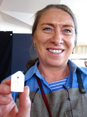 Woman holding up a tiny pottery house.