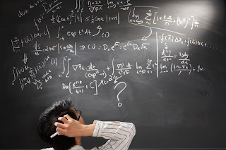 Man looking at difficult equation on chalkboard