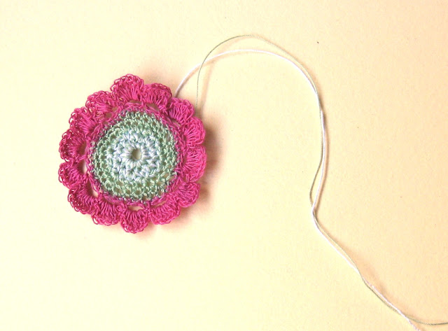 A crocheted flower worked in fine size 80 thread designed by Jodiebodie. The 40 mm diameter flower has a 22 mm green centre disk, with 14 hot pink petals around it. Two threads can be seen to the right of the flower which will be used to attach the flower to a card.
