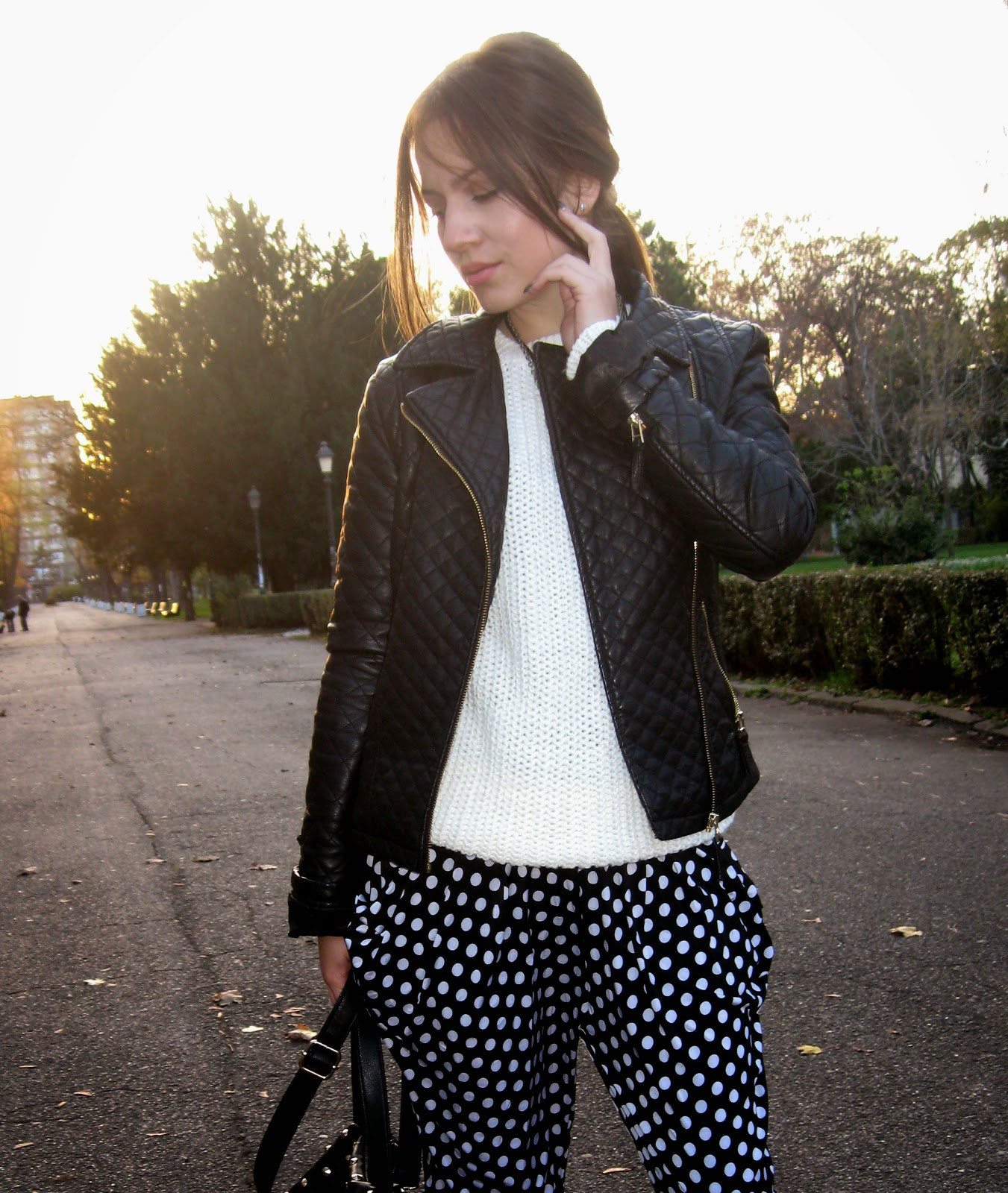 outfit, baggy pants with polka dots, black faux leather jacket, white chunky knit sweater, carpisa black studded bag