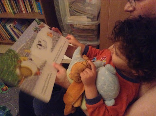 My boy with Daddy reading a book with his beloved elephant and bear toys
