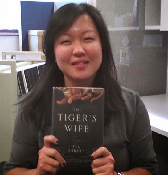 Ms. Chi holding a copy of The Tiger's Wife, a book by Tea Obreht