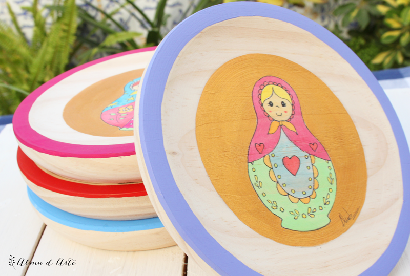 Matrioskas de colores pintadas sobre tabla