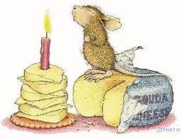 une souris souffle une bougie d'anniversaire sur un gateau de fromages