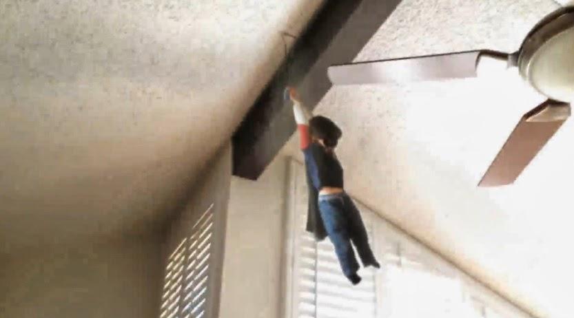 Un niño colgando en el techo emulando al superhéroe Batman