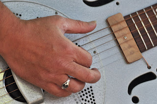 Close up of hand plucking resonator guitar strings
