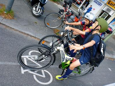 Zwei Schüler mit Fahrradhelmen quatschen auf dem Radstreifen
