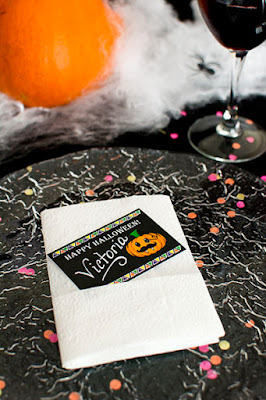 Halloween table decorated with a black table cloth, spider web and plastic black spiders, bright orange pumpkin and pink, orange and yellow confetti. Crackled glass dish with a black place card tucked into a white napkin.