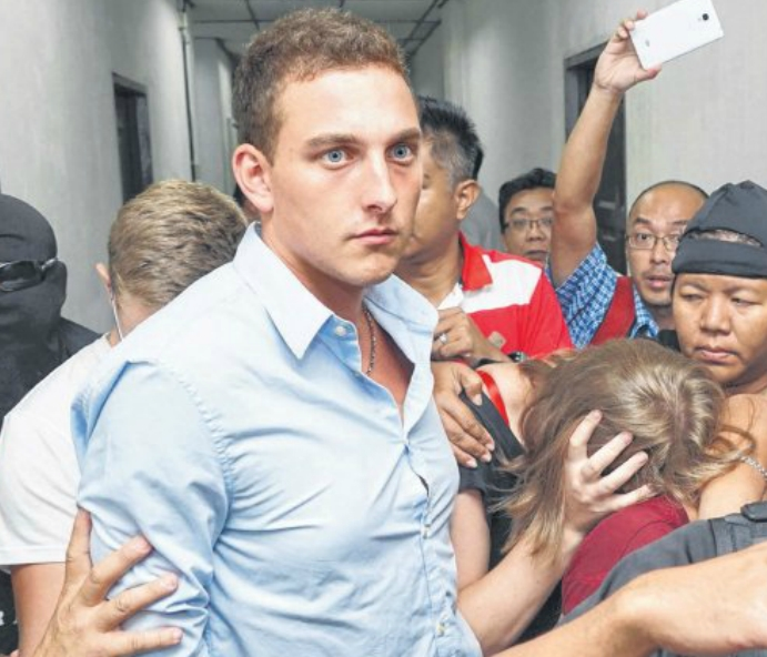 JAILED: Dutch national Dylan Snel (centre) leaving a court hearing along with three other hikers in Kota Kinabalu on June 12. The four took naked photos of themselves at the summit plateau of Mount Kinabalu.