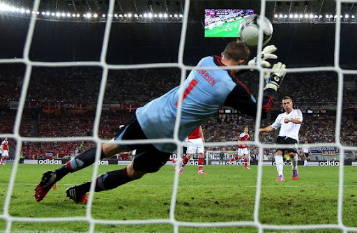 Denmark goalkeeper Stephan Andersen fails to save a goal from Germany fprward Lukas Podolski
