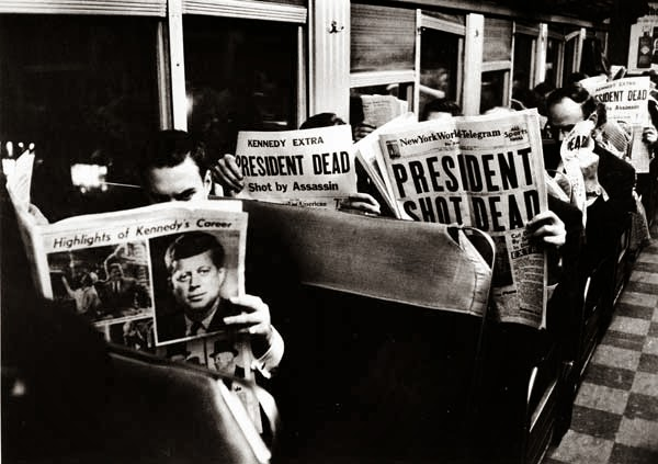 Train passengers read John F. Kennedy Assassinated Newspaper headlines
