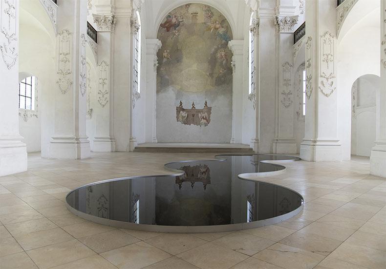 Delgadas piscinas llenas con aceite de motor utilizado reflejan el esplendor arquitectónico de una iglesia suiza