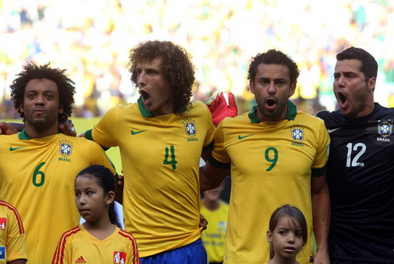 Marcelo, David Luiz, Fred, and Julio César are seen singing Brazil's national anthem