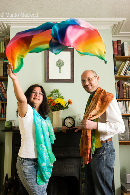 Neelam & Andrew (the LitB directors) are standing either side of a fireplace.  Neelam is throwing a colourful scarf into the air