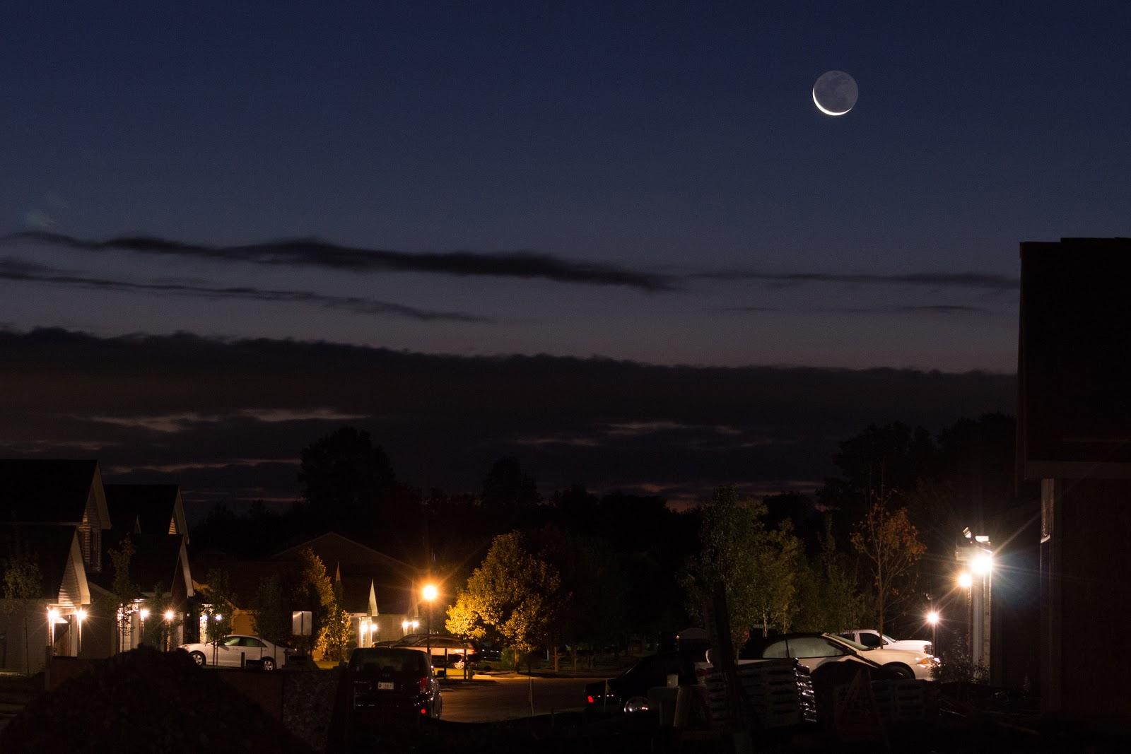 moon with earthshine over street