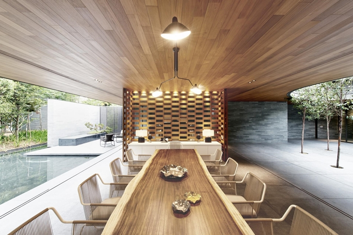 Wooden dining table in The Wall House by FARM Architects
