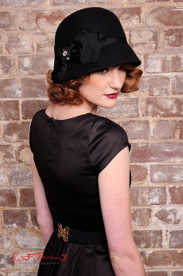 Vintage fashion, black dress and cloche hat -mid shot of red haired model - photographed against a distressed brick wall in the studio - studio fashion photography