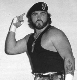 WWF wrestler Corporal Kirchner wearing a beret, tank top and dog tags