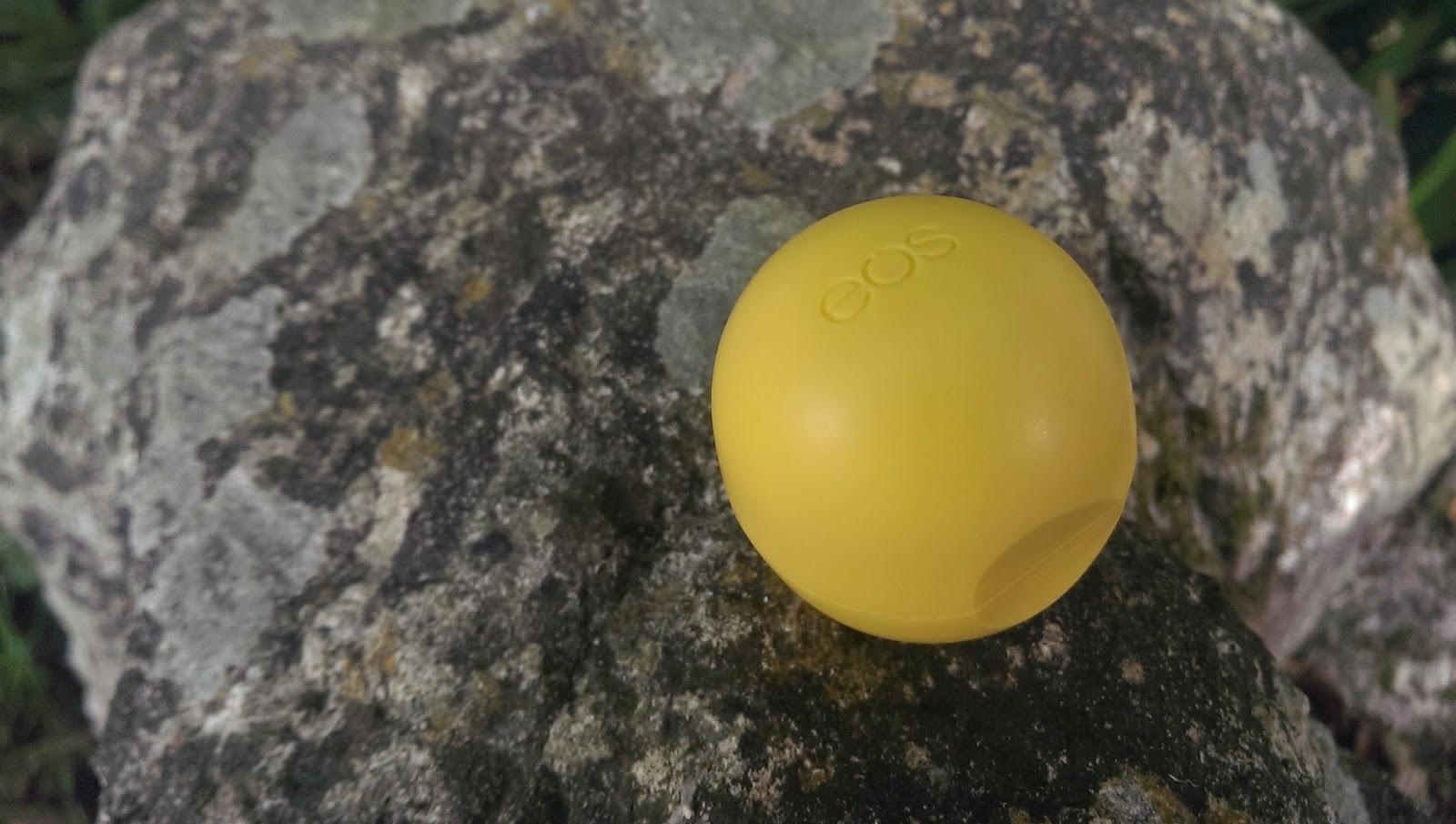 Lemon drop EOS lip balm closed and on a rock