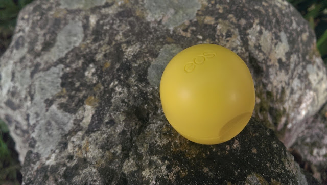 A Lemon drop EOS lip balm closed and on a rock