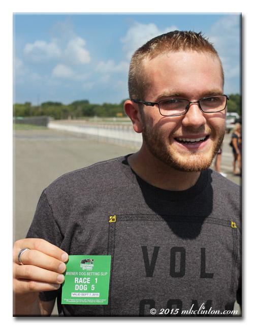 Man holding winning Weiner Dog Race ticket